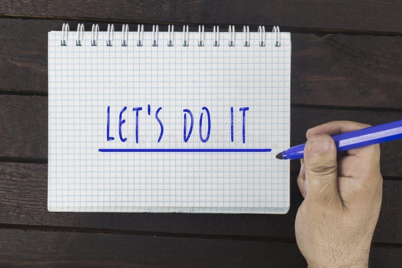 Χέρι που γράφει στο σημειωματάριο: Αφήστε ` s το κάνει στοκ εικόνα με δικαίωμα ελεύθερης χρήσης
