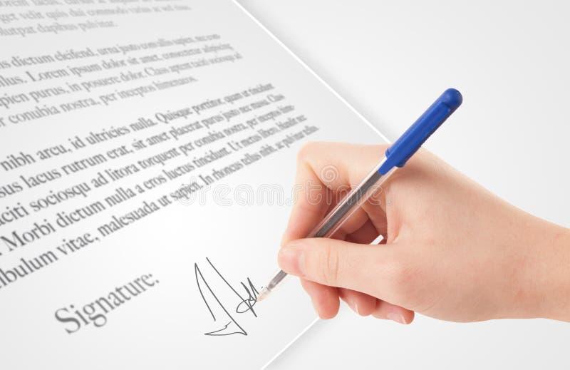 Χέρι που γράφει την προσωπική υπογραφή σε ένα έντυπο στοκ εικόνα