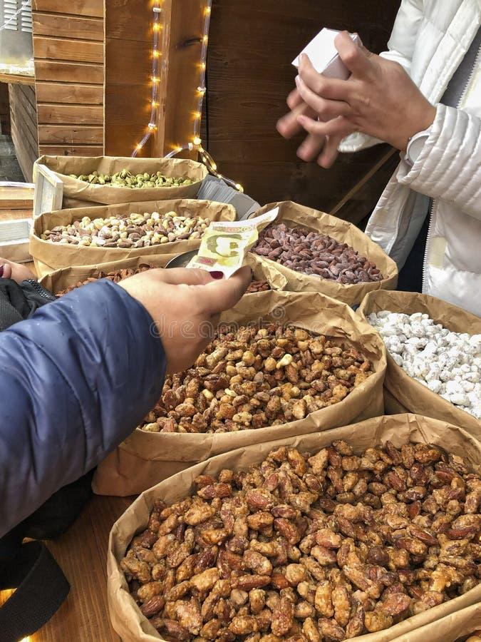 Χέρι που δίνει τα χρήματα για τους ξηρούς καρπούς και τα καρύδια στην α στοκ εικόνες με δικαίωμα ελεύθερης χρήσης