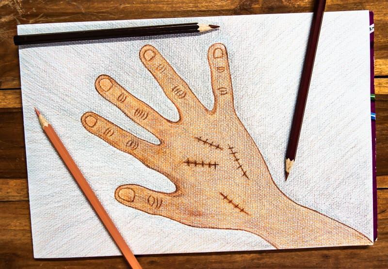 Χέρι που επισύρεται την προσοχή δεξί με τη χειρουργική συρραφή πληγών από τα ξύλινα μολύβια χρώματος στο υπόβαθρο της Λευκής Βίβλ στοκ εικόνα με δικαίωμα ελεύθερης χρήσης