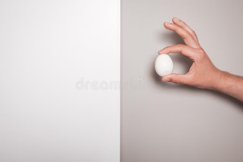 Χέρι που κρατά ένα αυγό σε ένα διπλό χρωματισμένο κλίμα στοκ φωτογραφία με δικαίωμα ελεύθερης χρήσης