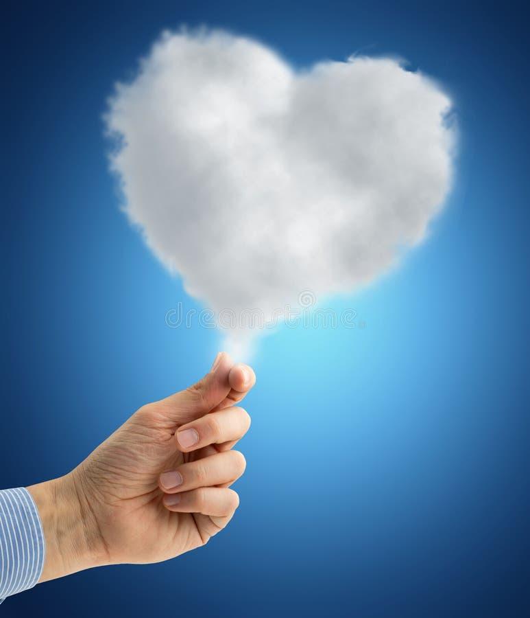 Χέρι που κρατά ένα καρδιά-διαμορφωμένο σύννεφο ελεύθερη απεικόνιση δικαιώματος