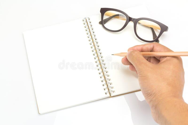 Χέρι που κρατά ένα μολύβι με τα γυαλιά σημειωματάριων και ματιών στοκ εικόνα με δικαίωμα ελεύθερης χρήσης