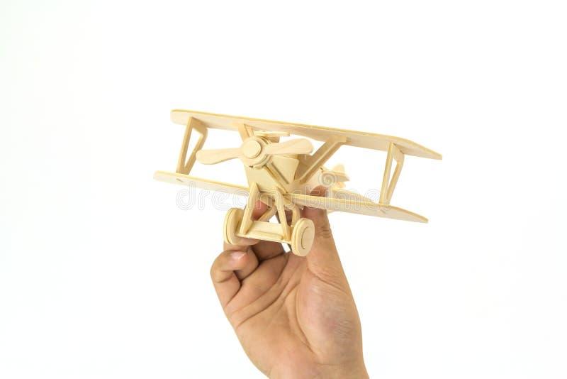 Χέρι που κρατά ένα ξύλινο πρότυπο αεροπλάνων στοκ εικόνα