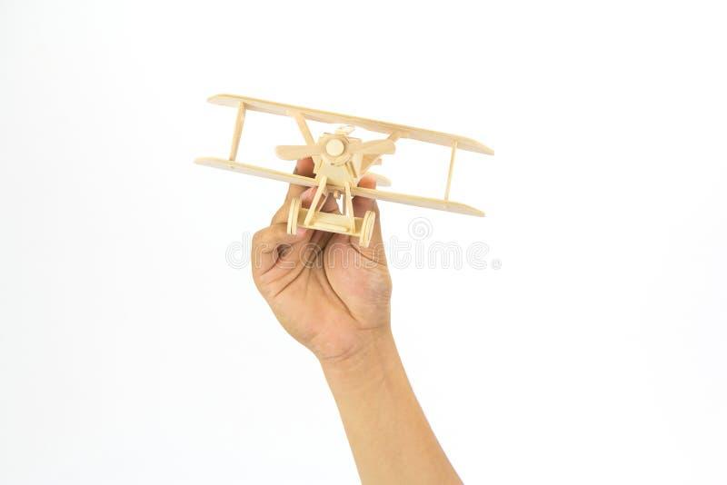 Χέρι που κρατά ένα ξύλινο πρότυπο αεροπλάνων στοκ φωτογραφία