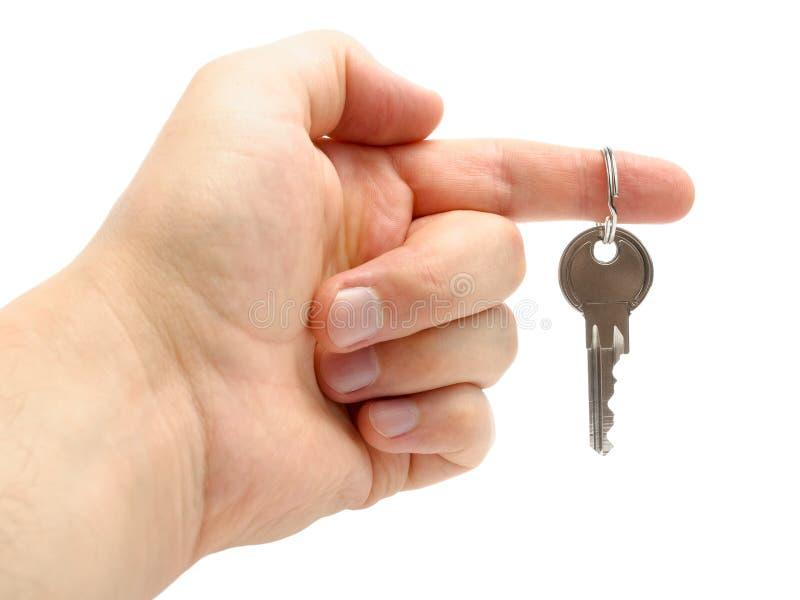 Χέρι που κρατά ένα πλήκτρο απομονωμένο στην άσπρη ανασκόπηση στοκ εικόνες με δικαίωμα ελεύθερης χρήσης