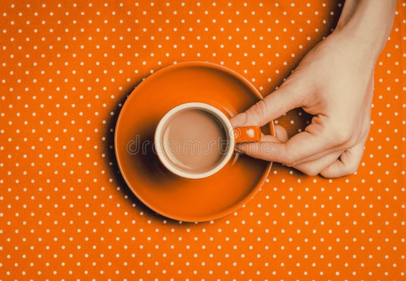 Χέρι που κρατά ένα πορτοκαλί φλιτζάνι του καφέ με το γάλα στοκ εικόνες