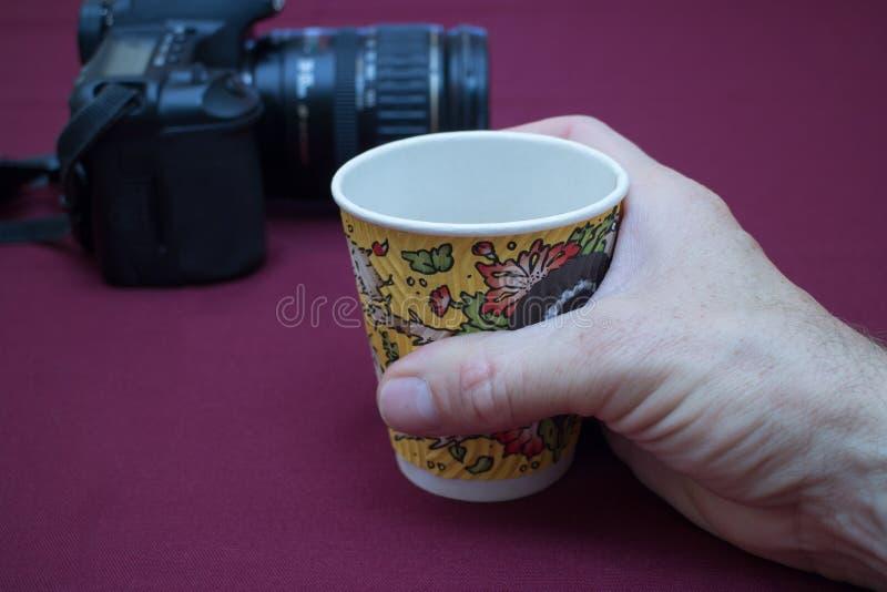 Χέρι που κρατά ένα φλιτζάνι του καφέ εγγράφου στοκ φωτογραφία με δικαίωμα ελεύθερης χρήσης