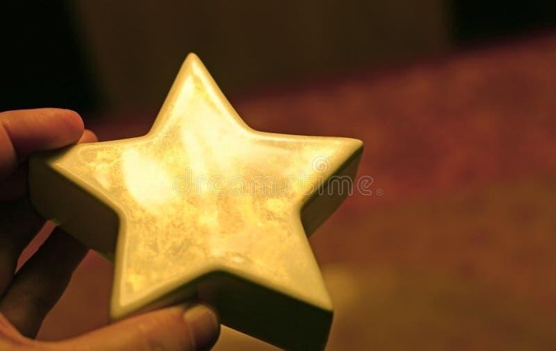Χέρι που κρατά ένα χρυσό λαμπυρίζοντας αστέρι στοκ φωτογραφίες με δικαίωμα ελεύθερης χρήσης