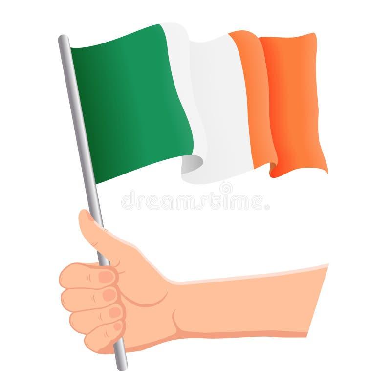 Χέρι που κρατά και που κυματίζει τη εθνική σημαία της Ιρλανδίας Ανεμιστήρες, ημέρα της ανεξαρτησίας, πατριωτική έννοια r απεικόνιση αποθεμάτων
