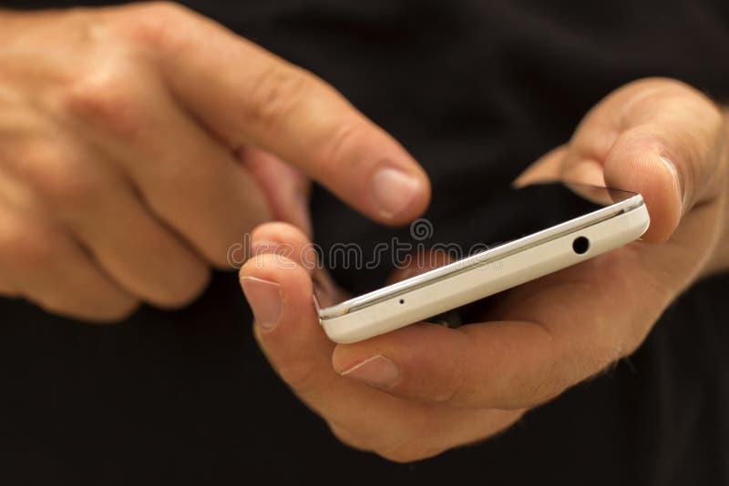 Χέρι που κρατά και που χρησιμοποιεί ένα smartphone/ένα τηλέφωνο στοκ εικόνα με δικαίωμα ελεύθερης χρήσης