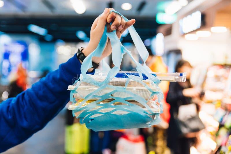 Χέρι που κρατά μια τέμνουσα τσάντα εγγράφου για το κιβώτιο γεύματος από το ψιλικατζίδικο με το υπόβαθρο θαμπάδων στη Ταϊπέι, Ταϊβ στοκ φωτογραφίες