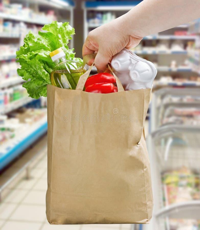 Χέρι που κρατά μια τσάντα εγγράφου με τα παντοπωλεία στοκ φωτογραφία