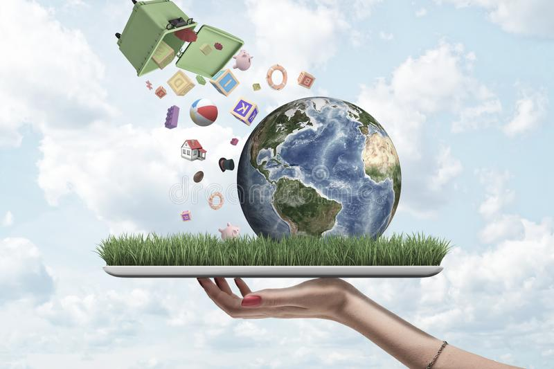 Χέρι που κρατά την ψηφιακή ταμπλέτα με την ανάπτυξη χλόης στην οθόνη και λίγη γη σε το, και dumpster κατρακυλημένος στον αέρα από στοκ εικόνα