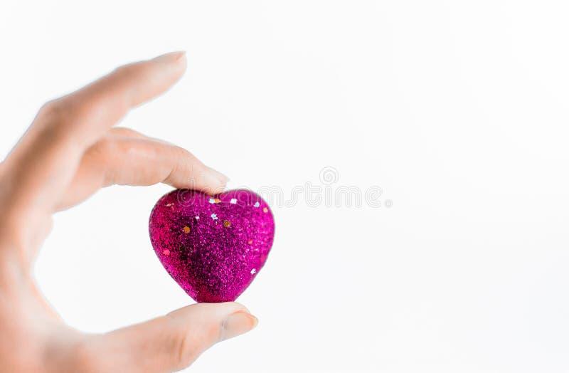 Χέρι που κρατά τις μίνι καρδιές στο άσπρο υπόβαθρο στοκ εικόνες με δικαίωμα ελεύθερης χρήσης