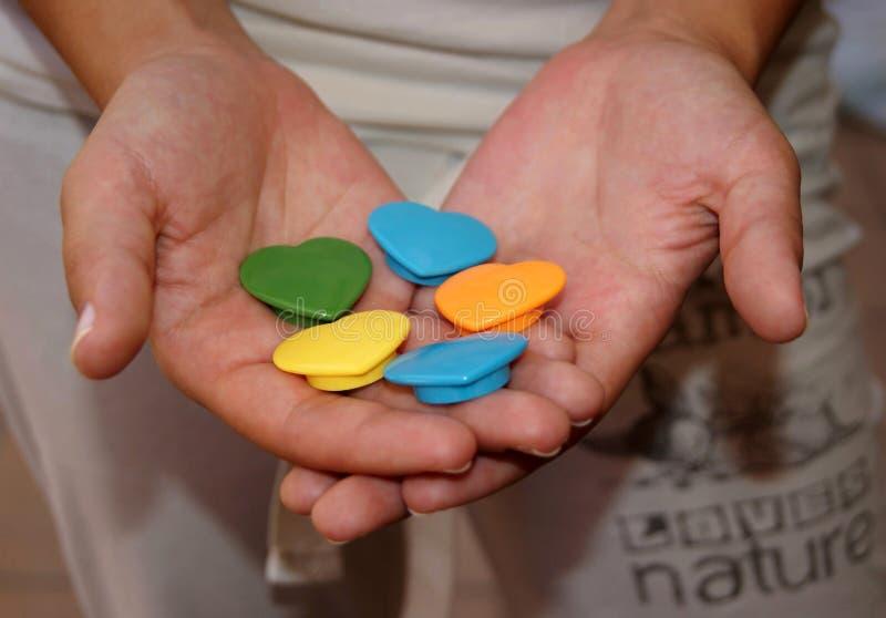 Χέρι που κρατά τις μικροσκοπικές χρωματισμένες καρδιές στοκ εικόνες