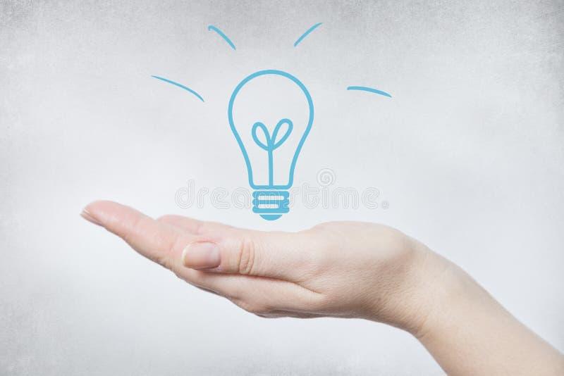 Χέρι που κρατά τον μπλε βολβό στοκ φωτογραφίες