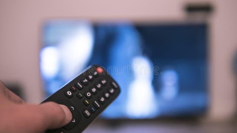 Χέρι που κρατά τον τηλεχειρισμό μπροστά από μια TV στοκ φωτογραφίες με δικαίωμα ελεύθερης χρήσης
