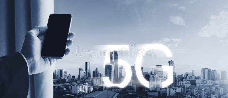 Χέρι που κρατά το κινητό έξυπνο τηλέφωνο, με το ασύρματο σήμα 5G Διαδίκτυο στην πόλη στοκ εικόνα