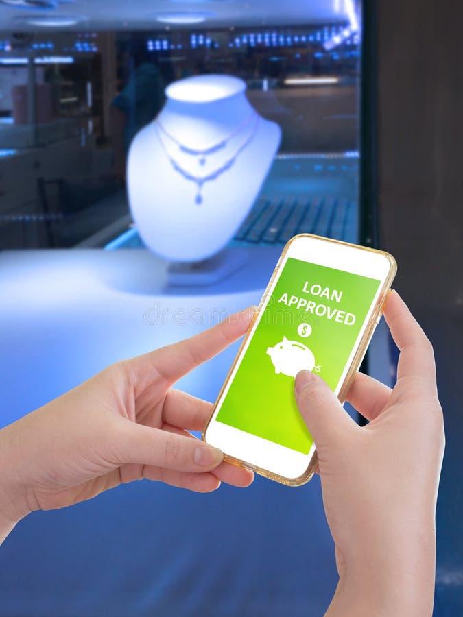 Χέρι που κρατά το κινητό τηλέφωνο με εγκεκριμένη τη δάνειο λέξη στοκ φωτογραφία
