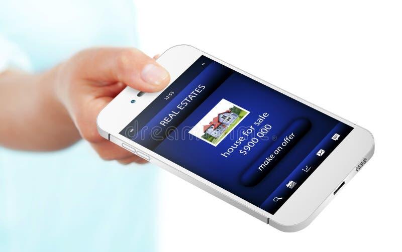 Χέρι που κρατά το κινητό τηλέφωνο με την προσφορά ακίνητων περιουσιών που απομονώνεται άνω του W στοκ εικόνες
