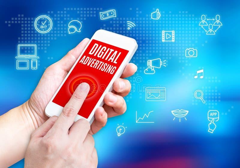 Χέρι που κρατά το κινητό τηλέφωνο με την ψηφιακή λέξη διαφήμισης με το rel στοκ εικόνες