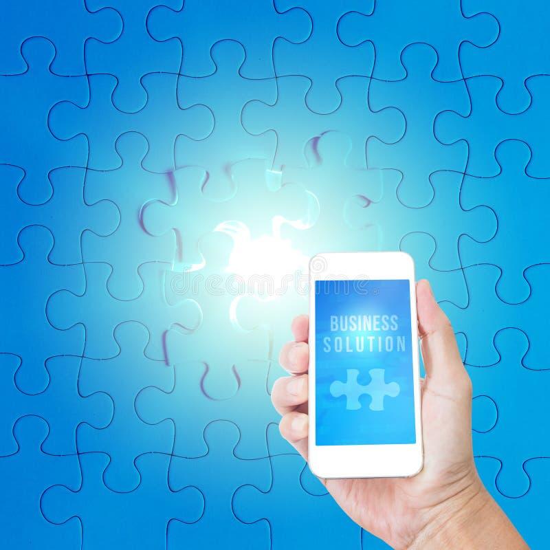 Χέρι που κρατά το κινητό τηλέφωνο με τη λέξη επιχειρησιακής λύσης στοκ φωτογραφία με δικαίωμα ελεύθερης χρήσης