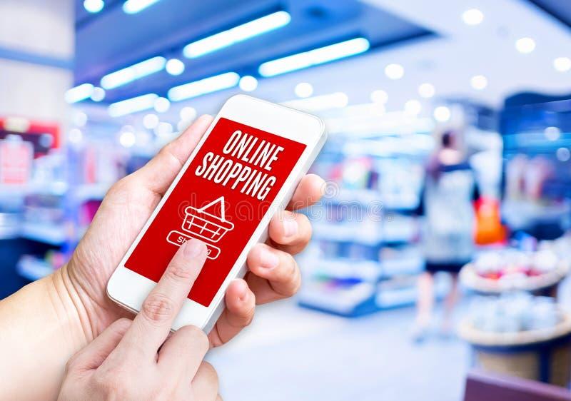Χέρι που κρατά το κινητό τηλέφωνο με τη σε απευθείας σύνδεση λέξη αγορών με θολωμένος στοκ φωτογραφία