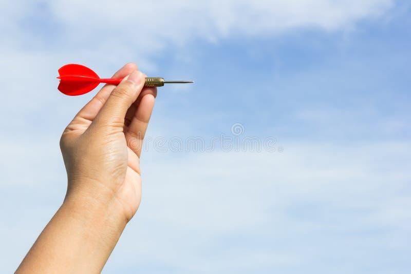 Χέρι που κρατά το κόκκινο βέλος στο υπόβαθρο ουρανού στοκ εικόνες
