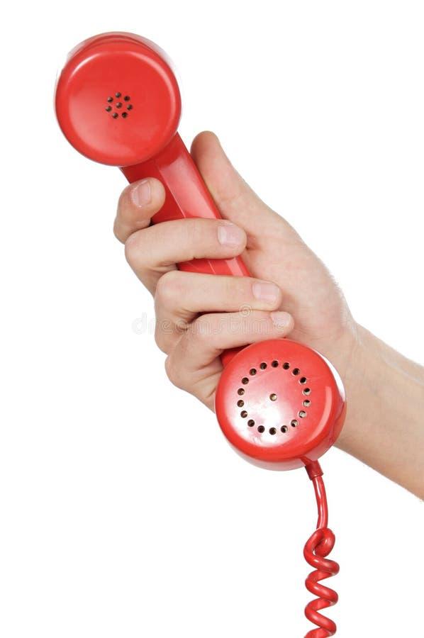 χέρι που κρατά το κόκκινο τηλέφωνο στοκ εικόνες