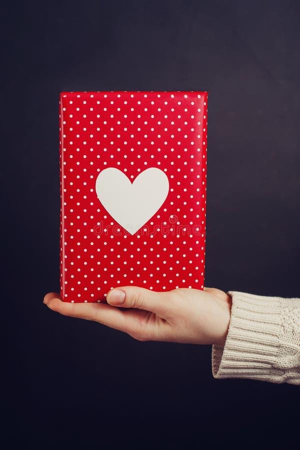 Χέρι που κρατά το κόκκινο δώρο στο Μαύρο στοκ φωτογραφίες