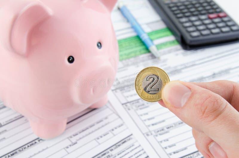 Χέρι που κρατά το πολωνικό νόμισμα Πολωνικές φορολογικές μορφές στο υπόβαθρο στοκ φωτογραφία