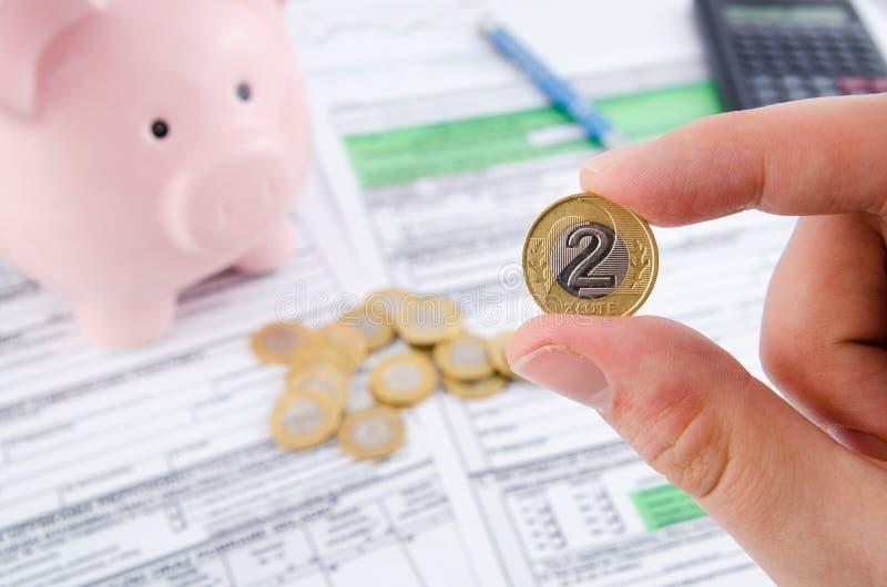 Χέρι που κρατά το πολωνικό νόμισμα Πολωνικές φορολογικές μορφές στο υπόβαθρο στοκ εικόνες