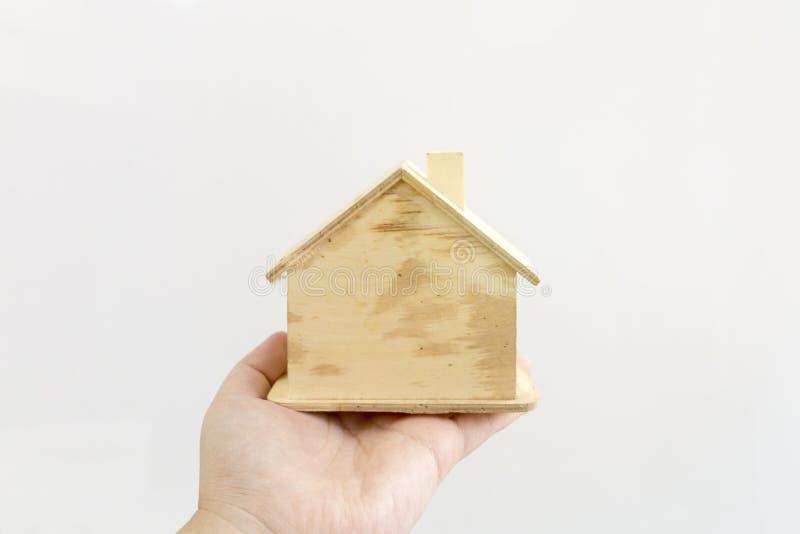 Χέρι που κρατά το πρότυπο ξύλινο σπίτι στο άσπρο υπόβαθρο Σκέψη και όνειρο στοκ εικόνες