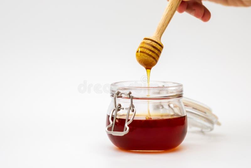 Χέρι που κρατά dripper μελιού στο άσπρο υπόβαθρο φρέσκια ελιά πετρελαίου κουζινών τροφίμων έννοιας αρχιμαγείρων πέρα από την έκχυ στοκ εικόνες