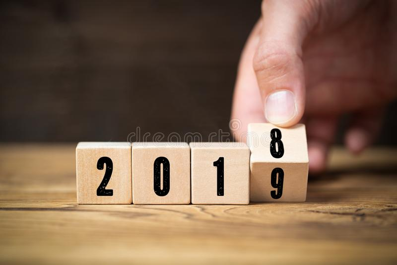 Χέρι που κτυπά έναν κύβο, symbolizng η αλλαγή από το 2018 ως το 2019 στοκ φωτογραφία