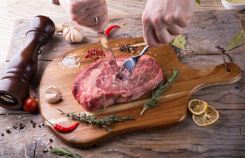 Χέρι που κόβει την ακατέργαστη μπριζόλα βόειου κρέατος στοκ φωτογραφία με δικαίωμα ελεύθερης χρήσης