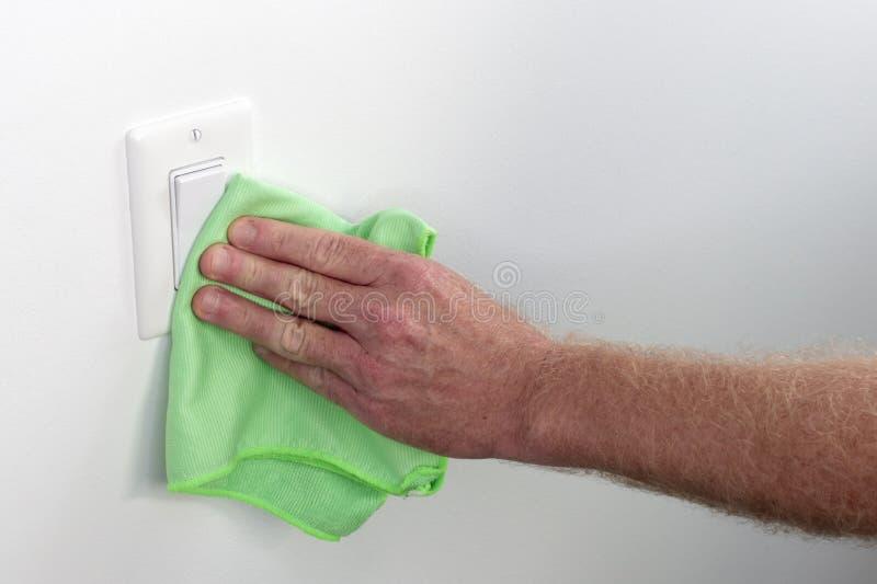 Χέρι που ξεσκονίζει και που καθαρίζει την επίπεδη ελαφριά επιτροπή διακοπτών στοκ εικόνες