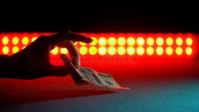 Χέρι που παίρνει τα πεσμένα χρήματα από το στάδιο, αποδοχές στο νυχτερινό κέντρο διασκέδασης, ενήλικη ψυχαγωγία στοκ φωτογραφίες