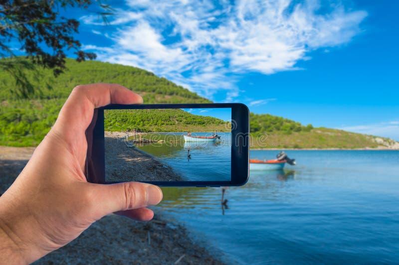 Χέρι που παίρνει την εικόνα με ένα smartphone στην ακτή στην ηλιόλουστη ημέρα του καλοκαιριού στοκ εικόνα