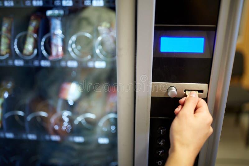 Χέρι που παρεμβάλλει το ευρο- νόμισμα στην αυλάκωση μηχανών πώλησης στοκ εικόνες