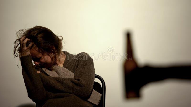 Χέρι που παρουσιάζει μπουκάλι με την εθισμένη οινόπνευμα γυναίκα μπύρας, αποκατάσταση, willpower στοκ φωτογραφία