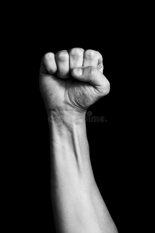 Χέρι που παρουσιάζει πυγμή πυγμών ενός ατόμου που ανατρέφεται επάνω σε ένα μαύρο υπόβαθρο στοκ εικόνα με δικαίωμα ελεύθερης χρήσης