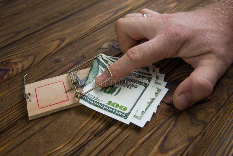 Χέρι που πιάνεται σε μια ποντικοπαγήδα με το τραπεζογραμμάτιο εκατό δολαρίων στοκ φωτογραφία με δικαίωμα ελεύθερης χρήσης
