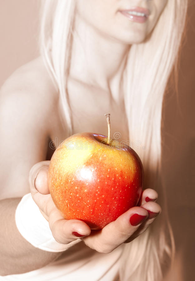 Χέρι που προτείνει να πάρει το μήλο στοκ εικόνα