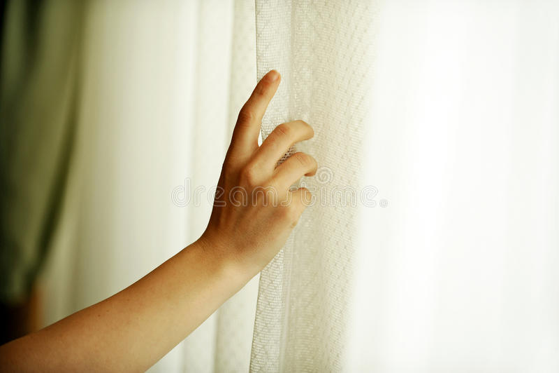 Χέρι που τραβά μια κουρτίνα παραθύρων στοκ εικόνες