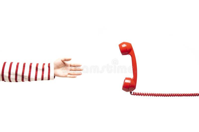 Χέρι που φθάνει στο κόκκινο τηλέφωνο στοκ εικόνα με δικαίωμα ελεύθερης χρήσης