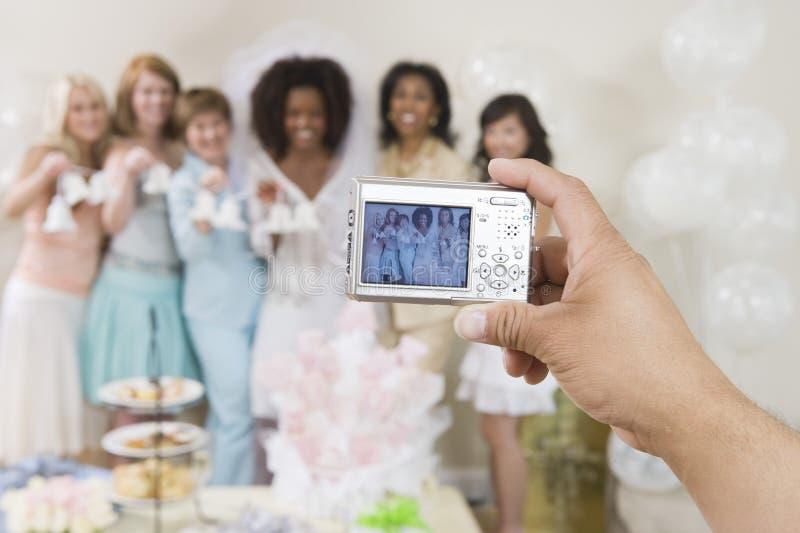 Χέρι που φωτογραφίζει τα γαμήλια κουδούνια εκμετάλλευσης γυναικών στοκ εικόνα με δικαίωμα ελεύθερης χρήσης