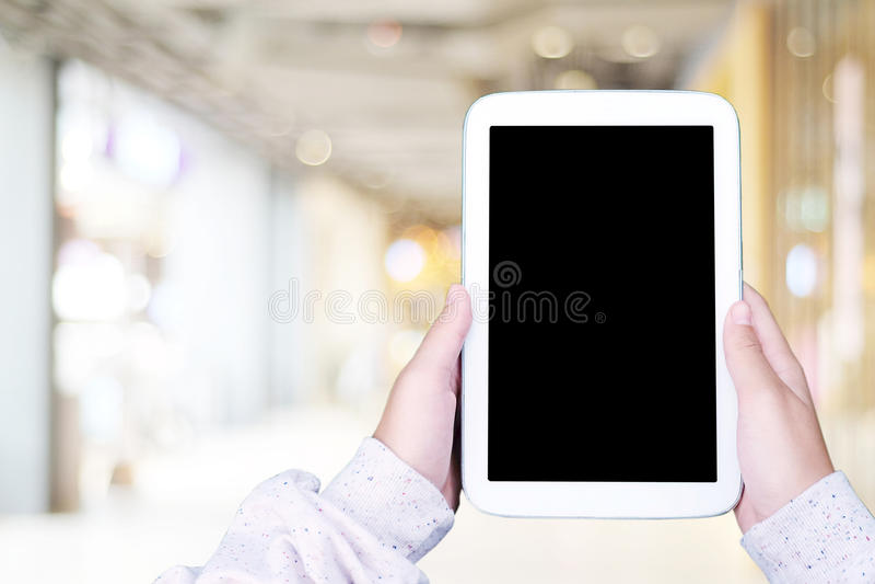 Χέρι που χρησιμοποιεί την κενή ταμπλέτα οθόνης πέρα από το κατάστημα θαμπάδων με το bokeh backgr στοκ φωτογραφία