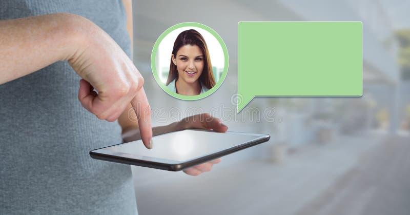 Χέρι που χρησιμοποιεί την ταμπλέτα με το σχεδιάγραμμα μηνύματος φυσαλίδων συνομιλίας στοκ εικόνες